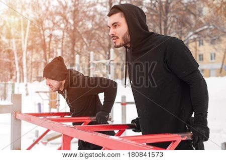 Two sporty men doing exercises on parallel bars. Young adults doing triceps dips. Winter fitness.