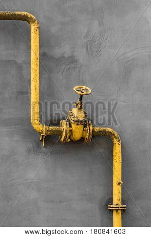 Old gas gate of yellow colour is on a pipe and blocks a pipe. The pipeline with cranes for gas giving on the wall.