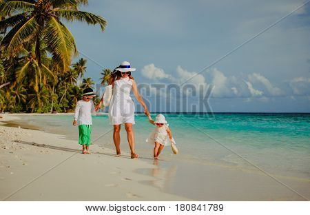 mother with little son and daughter walk on tropical beach