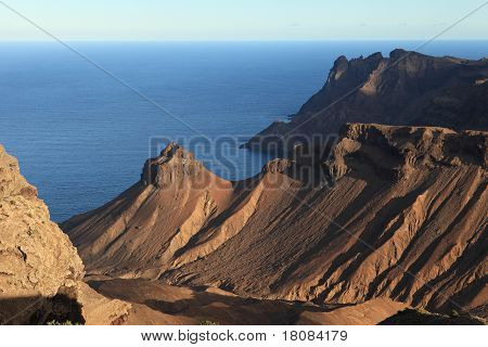 The rugged volcanic terrain of St Helenas coastline. Foreground shows Turks Cap peak and Coxs Battery point. Background peaks in shadow are King and Queen Rocks at Prosperous Bay. poster