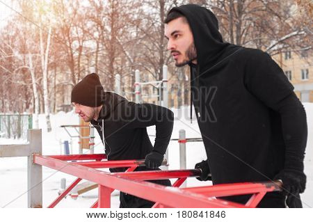 Two male adults working out on parallel bars. Winter fitness