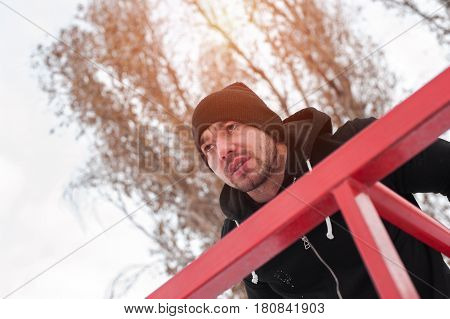 Young sporty adult exercising on parallel bars. Winter fitness.