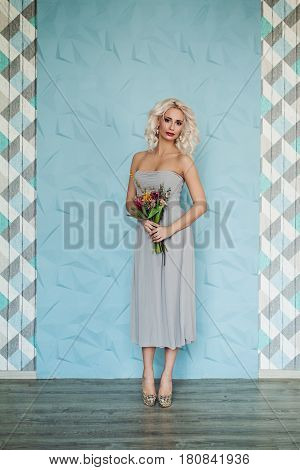 Beauty Fashion Portrait of Glamorous Blonde Model Woman Blonde Curly Hair and Flowers on Blue Background