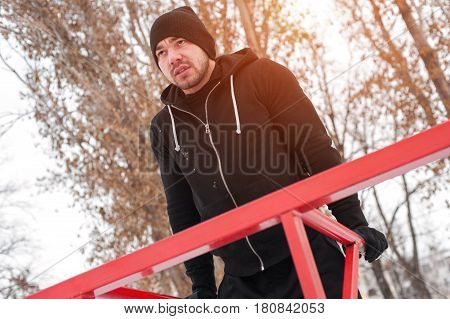 Winter fitness workout. Young handsome man in black sportswear doing triceps dips on parallel bars outdoors.