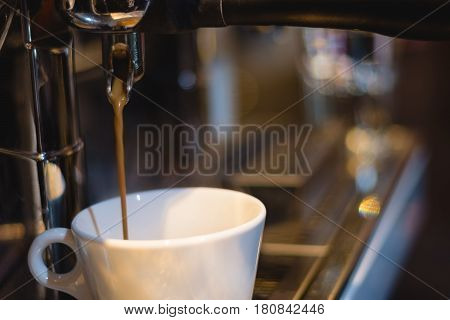 caramel coffee pouring from coffee machine into a cup in coffee shop