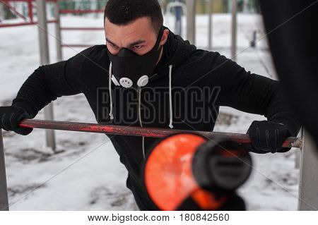 Young man wearing high altitude mask exercising on bars outdoors while fitness coach motivating him via loudspeaker.