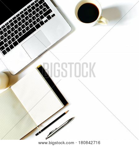 Stylish feminine work place. White office desk table with laptop, roses, vintage white tray, notebook, coffee cup, pen and pencil. Top view with copy space, flat lay