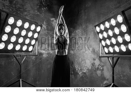 black and white portrait of beautiful attractive blonde young woman dancer on the stage with lights in loft background dancing free dance
