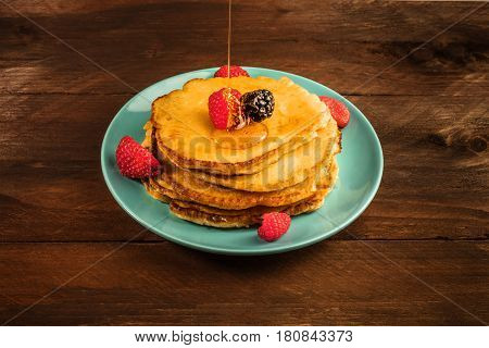 A photo of honey poured over homemade pancakes with fresh strawberry, raspberry, and blackberry, on a dark brown wooden texture with copy space