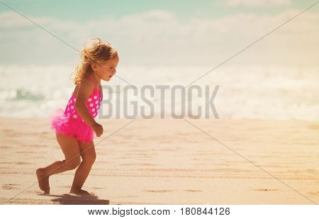 happy little girl running on tropical beach