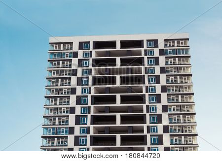 Modern and new apartment building. Photo of a tall block of flats with balconies against a blue sky.