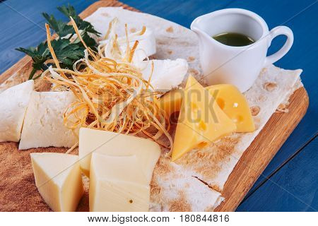 Cheese platter and sauce on wooden platter.