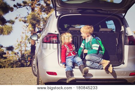 cute little boy and girl travel by car on road in nature