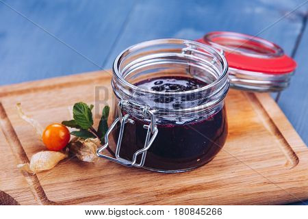 Berry jam. Glass jar of berry jam on blue background. Preserved fruits. Homemade berry jam in jar covered.