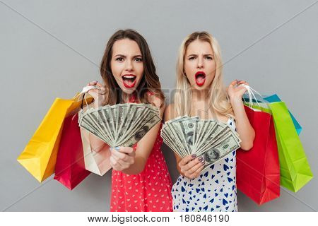 Two shocked women in dresses  holding shopping bags and showing money  at camera over gray background