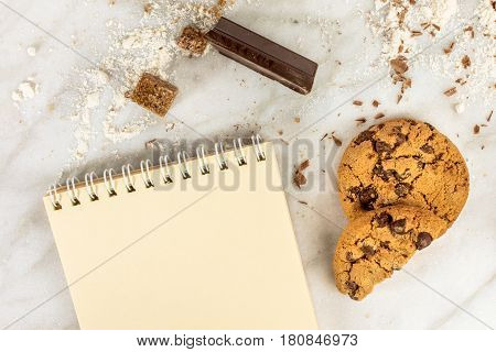 The process of making chocolate chips cookies. Overhead shot of biscuits with chocolate pieces, flour, and cane sugar around them, with a blank notepad for copy space
