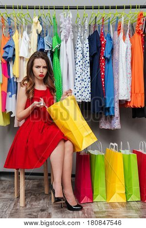 Unhappy young woman in red dress dissatisfied with content of her package