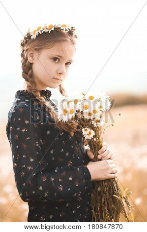 Stylish teenage girl 12-14 year old holding chamomile flowers outdoors in field. Looking away. Childhood.
