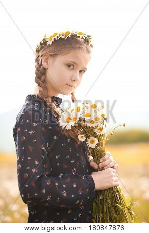 Smiling teenager girl 14-16 year old holding flowers outdoors. Looking at camera. Childhood.
