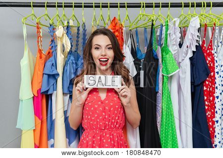 Brunette young woman showing at nameplate sale standing near hangers
