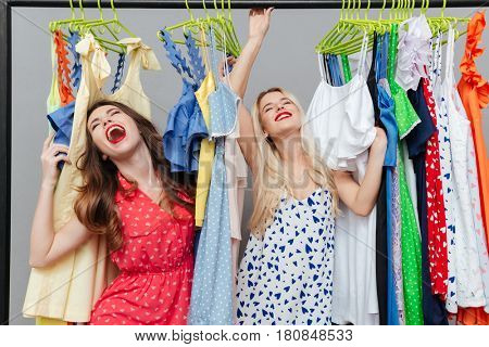 Happy glad young women standing near dresses and rejoicing