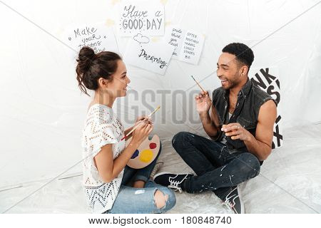 Picture of smiling young loving couple artists sitting on floor over white background. Looking aside.