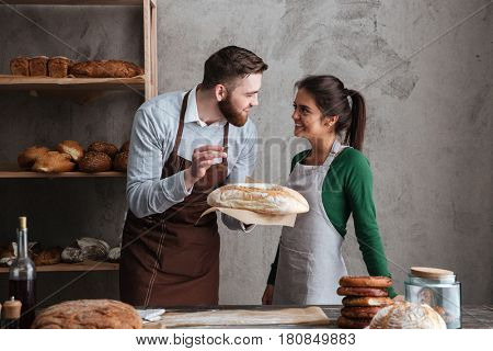 Image of smiling loving couple bakers standing at bakery holding bread. Looking aside.