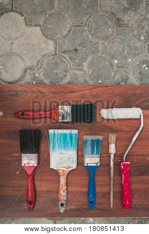 Multicolored brushes in paint lie on a wooden substrate and stone floor. Top view