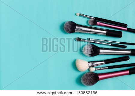 Beauty products, everyday make-up. Cosmetic brushes on bright blue background, flat lay, top view