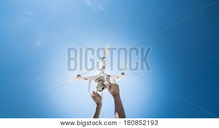 Closeup raised hands of woman holding drone over beautiful summer blue sky background