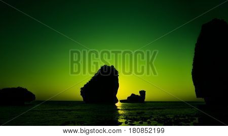 Camel Rock in Nui Bay at Phi Phi Don during lime green sunset, Thailand