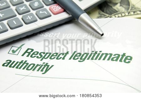Respect legitimate authority printed on book with pen and calculator