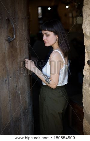 Brunette young tourist woman in green pants and white silk blouse opens old wooden door of artisanal cheesemonger