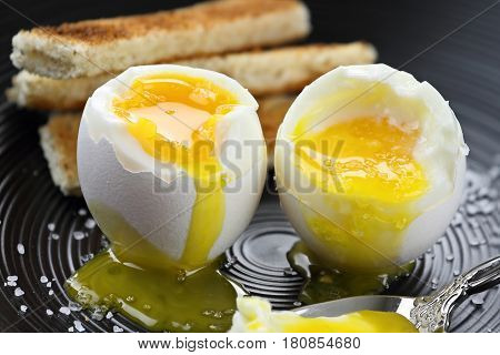 Two soft boiled eggs with toast soldiers in the background. Extreme shallow depth of field with selective focus.