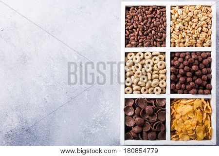 Variety of cold quick breakfast cereals in white wooden box, healthy eating concept with copy space. Top view.