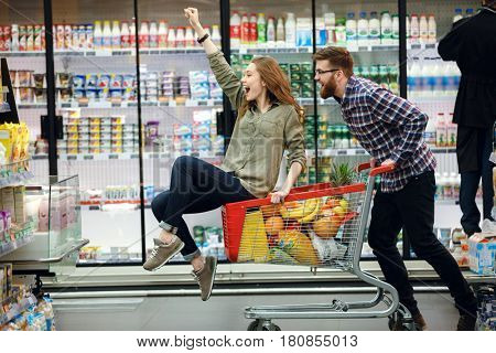 Happy couple having fun while choosing food in the supermarket. Young happy man pushing shopping cart with his girfriend inside