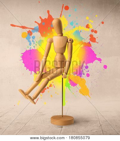 Wooden mannequin posed in front of a greyish background with colorful splashes behind it