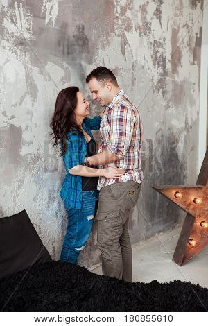 Portrait of beautiful young couple in casual clothes hugging and smiling, standing against gray wall.