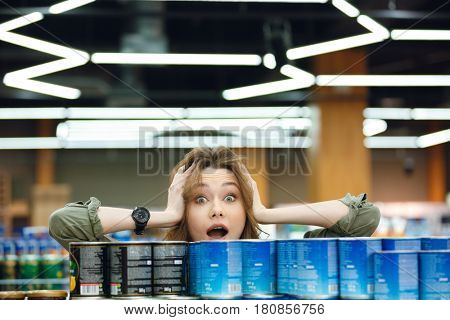 Close up portrait of a confused casual woman peeking out from the aisle in a supermarket and deciding what to buy