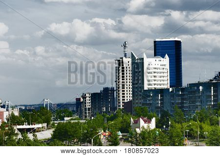 landscape within the city with high buildings against the background of dense white clouds