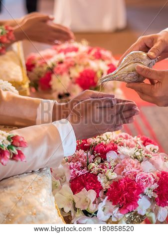Thai wedding ceremony, water pouring from conch shell to bless the groom and the bride