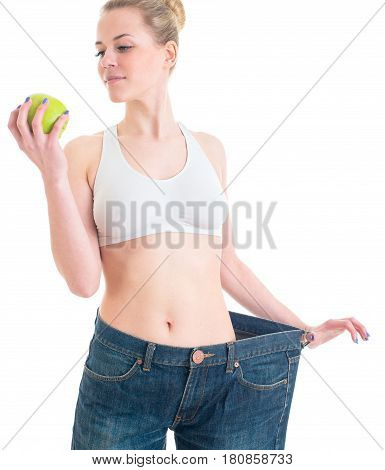 Sporty pretty woman showing big pants and apple. Sport fitness and diet concept. Isolated on white Background