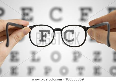 Hands holds black glasses in front of vision testing chart. Eye sight testing concept.