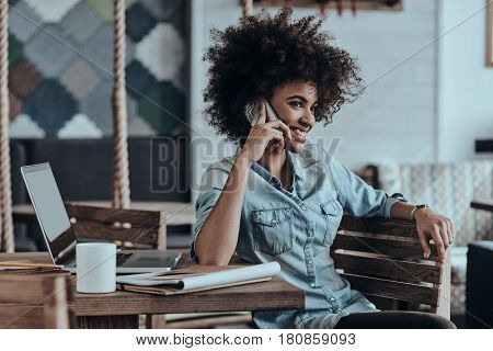 In touch with friends. Beautiful young African woman talking on smart phone and smiling while sitting in cafй or creative office