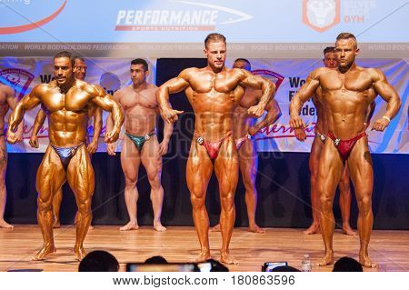 MAASTRICHT THE NETHERLANDS - OCTOBER 25 2015: Male bodybuilders flex their muscles and shows their best front pose on stage at the World Grandprix Bodybuilding and Fitness of the WBBF-WFF