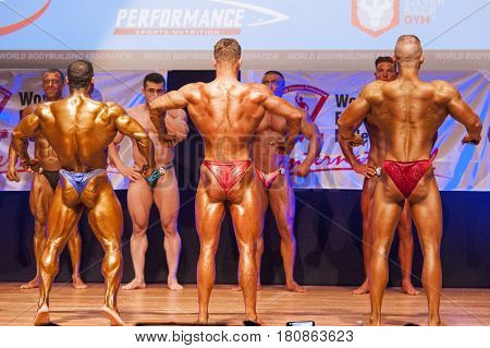 MAASTRICHT THE NETHERLANDS - OCTOBER 25 2015: Male bodybuilders flex their muscles and shows their best back pose on stage at the World Grandprix Bodybuilding and Fitness of the WBBF-WFF