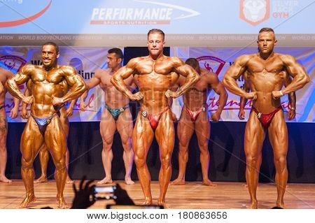 MAASTRICHT THE NETHERLANDS - OCTOBER 25 2015: Male bodybuilders flex their muscles and shows their best lats spread front pose on stage at the World Grandprix Bodybuilding and Fitness of the WBBF-WFF