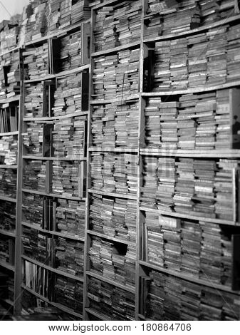 BLACK AND WHITE PHOTO OF BOOKS CRAMMED IN BOOKSHELVES AT BOOKSTORE