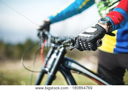 Close-up of a rider's hand in gloves on a mountain bike handlebars with shallow depth of field