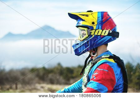 Portrait of a bicyclist in a full-face helmet and sunglasses against a background of a mountain that is hidden behind a low cloud cover